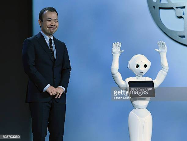 Vice President of Business Development for SoftBank Robotics Kenichi Yoshida looks on as SoftBank's emotionreading robot Pepper waves to the audience...