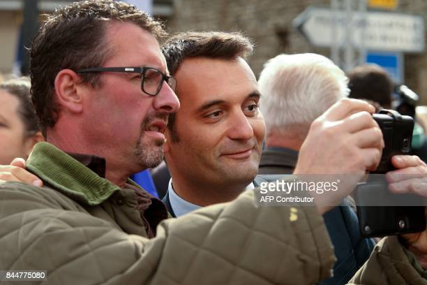 Vice president of France's National Front party Florian Philippot poses for a selfie photo with a supporter within a rally on September 9 2017 in...