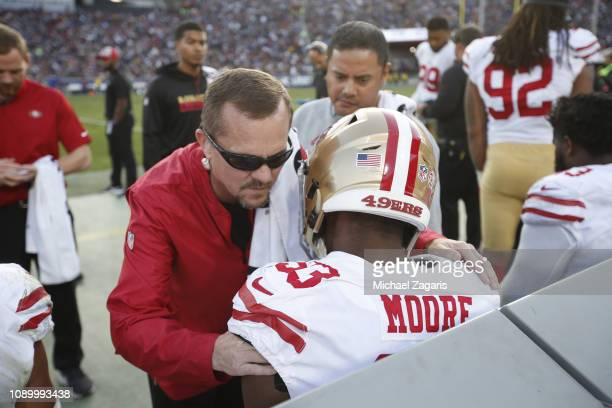 Vice President of Medical Services and Head Athletic Trainer Jeff Ferguson of the San Francisco 49ers works on Tarvarius Moore on the sideline during...
