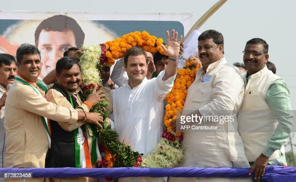 Vice President of the Indian National Congress party Rahul Gandhi waves while being garlanded during a political rally at Chilloda village some 40...