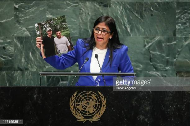 Vice President of Venezuela Delcy Rodriguez holds up a photo of Venezuelan opposition leader Juan Guaido with a suspected member of the paramilitary...