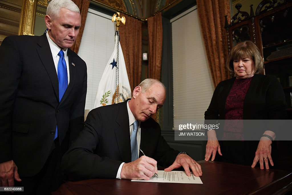 US Vice President President Mike Pence (L) looks on as General John Kelly (C) signs his conformation letter as US Secretary of Homeland Security in the Vice President's Ceremonial Office in Washington, DC, January 20, 2017. / AFP / JIM