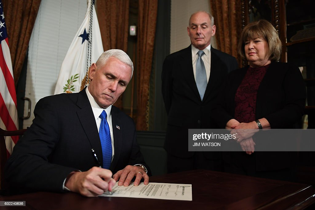 US Vice President President Mike Pence (L) signs General John Kelly's (C) conformation letter as US Secretary of Homeland Security in the Vice President's Ceremonial Office in Washington, DC, January 20, 2017. / AFP / JIM