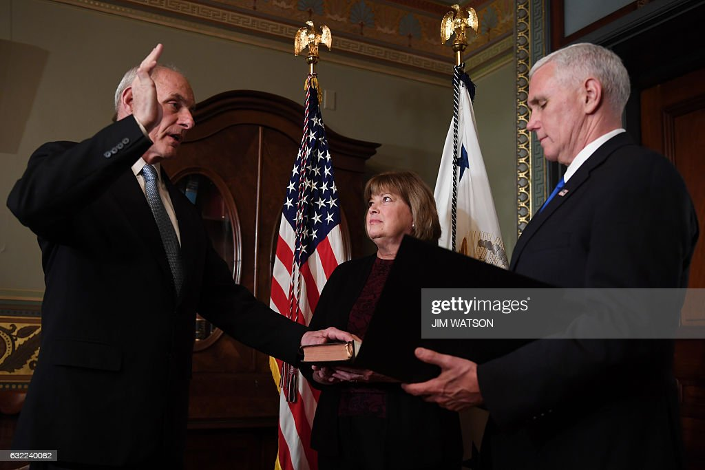 US Vice President President Mike Pence (R) swears in General John Kelly (L) as US Secretary of Homeland Security in the Vice President's Ceremonial Office in the Old Executive Office Building in Washington, DC, January 20, 2017. / AFP / JIM