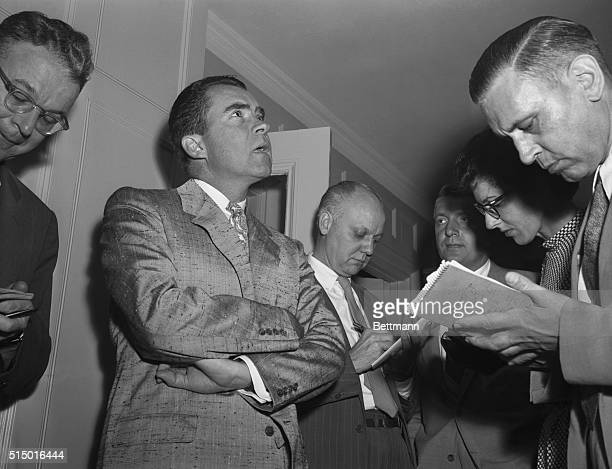 Vice President Richard M. Nixon is interviewed by newsmen after receiving a phone call from White House press secretary James Hagerty while attending...