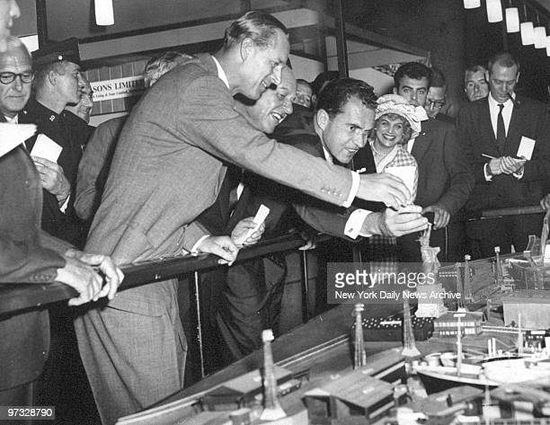 Vice President Richard Nixon is joined by Prince Phillip of England in putting back the torch on this scale model of the Statue of Liberty