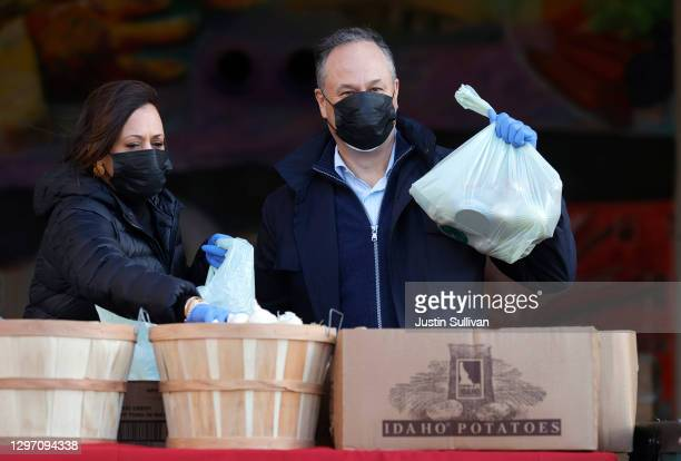 Vice President-elect Kamala Harris and her husband Doug Emhoff pack bags of food while volunteering at Martha's Table on January 18, 2021 in...