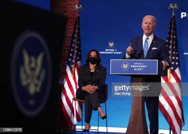 Vice President-elect Kamala Harris looks on as U.S. President-elect Joe Biden speaks as he lays out his plan for combating the coronavirus and...