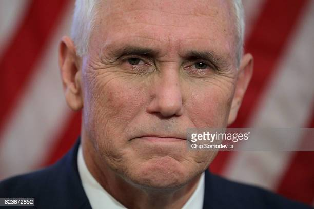 Vice Presidentelect Mike Pence listens to House Minority Leader Nancy Pelosi as they talk to reporters following a meeting in her offices at the US...