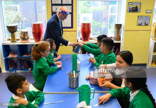 Vice Principal Tim Roach wears a PPE face shield as he supervises Year Four children eating lunch at Greenacres Primary Academy in Oldham, northern...