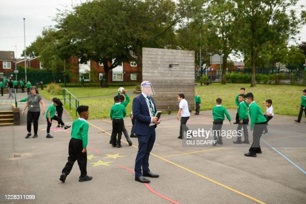 Vice Principal Tim Roach wears a PPE face shield in the playground at Greenacres Primary Academy in Oldham northern England on September 02 2020...