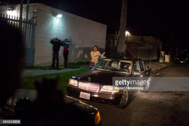 Vice squad officers with the Los Angeles Police Department draw their pistols on 4 people in a car January 31 2013 before they're searched arrested...