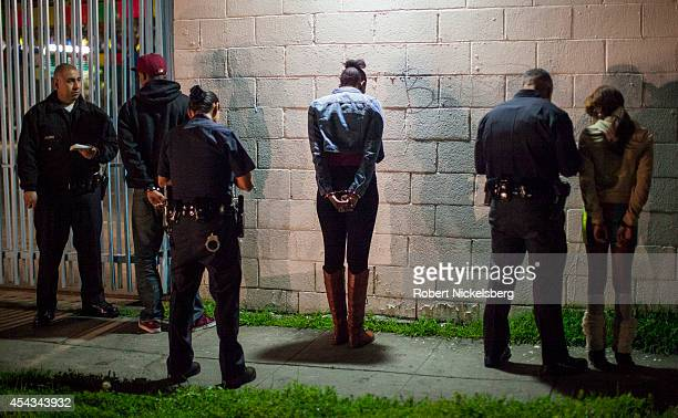 Vice squad officers with the Los Angeles Police Department take information from a handcuffed man 2nd left January 31 2013 and two women center and...
