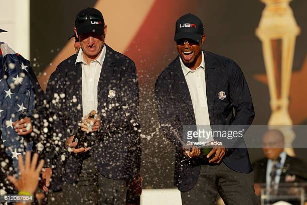 Vicecaptains Jim Furyk and vicecaptain Tiger Woods of the United States spray champagne after winning the Ryder Cup during the closing ceremony of...