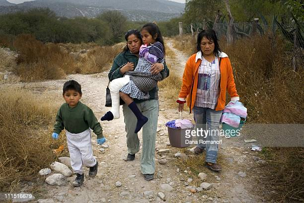 Vicenta Toribio Felipe and her neighbors return from bathing in the stream behind their home on December 14 2006 in Tasquillo The majority of the...