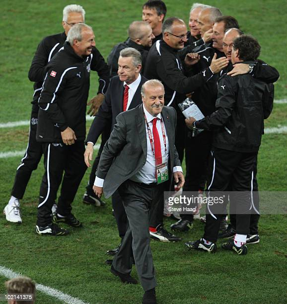 Vicente del Bosque head coach of Spain walks away as Ottmar Hitzfeld head coach of Switzerland and his coaching staff celebrate victory during the...