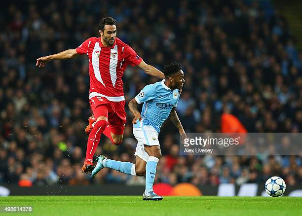 Vicente Iborra of Sevilla challenges Raheem Sterling of Manchester City during the UEFA Champions League Group D match between Manchester City and...