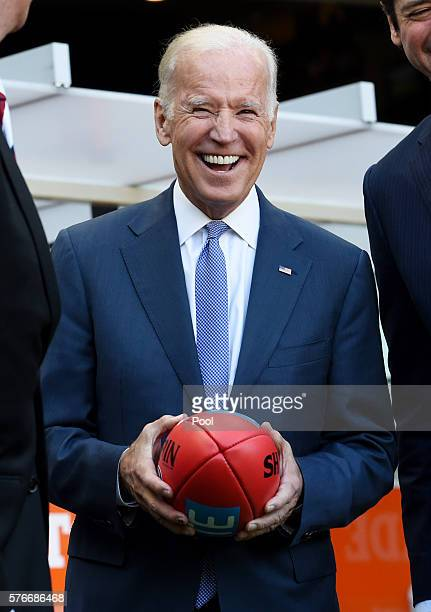 VicePresident Joe Biden holds an AFL football as he speaks to the AFL CEO Gillon McLachlan and Mike Fitzpatrick before the round 17 AFL match between...