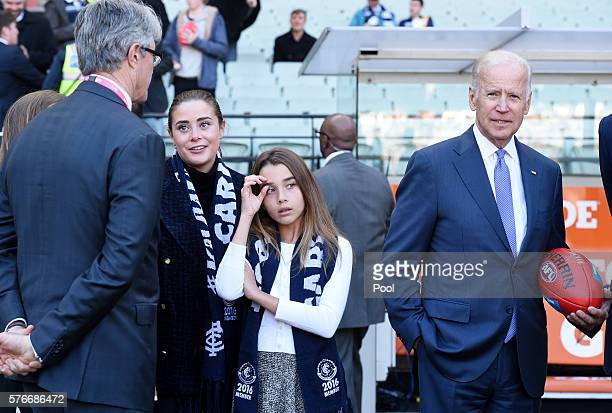 VicePresident Joe Biden holds an AFL football while his granddaughters Natalie and Naomi wear Carlton scarves before the round 17 AFL match between...