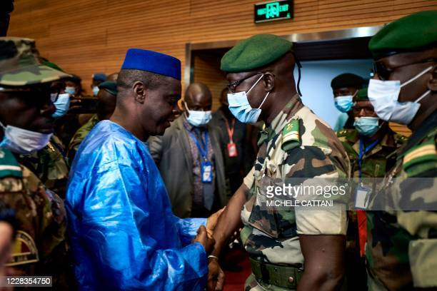 Vice-President of the CNSP Colonel Malick Diaw shakes hands with Issa Kaou Djim, a leading figure in the June 5 Movement, during a ceremony to open...