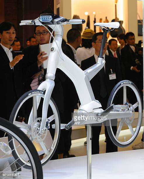 Vicitors look at Yamaha's 'PAS er' electrohybrid bicycle at the Tokyo Motor Show in Chiba on October 21 2009 Futuristic concept cars plugin hybrids...