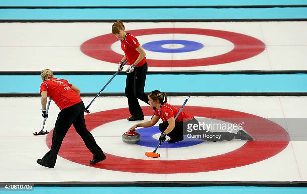 Vicki Adams of Great Britain plays a stone as Claire Hamilton and Anna Sloan assist during the Bronze medal match between Switzerland and Great...