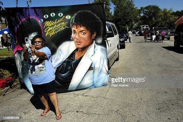 Vicki Hutson of Gary takes a picture of herself in front of a picture of the cover of Michael Jackson's Thriller album outside of his childhood home...
