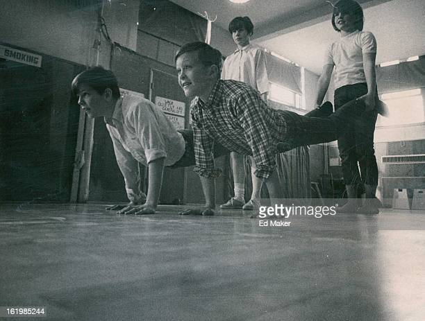 Vicki Kellogg of 1249 Allison St., left; and Barbara Carey of 8201 W. 9th Ave., hold the feet of David Shurtlaff of 810 Carr St., left, and Kirk...
