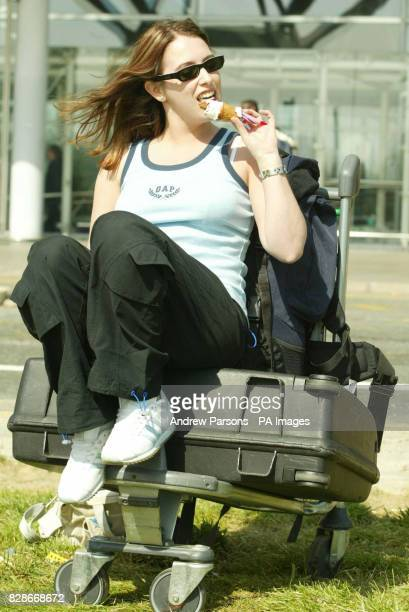 Vicki Leon a human resources student at Bournemouth University eats an ice cream while sunbathing at Stansted Airport in Essex before catching a...