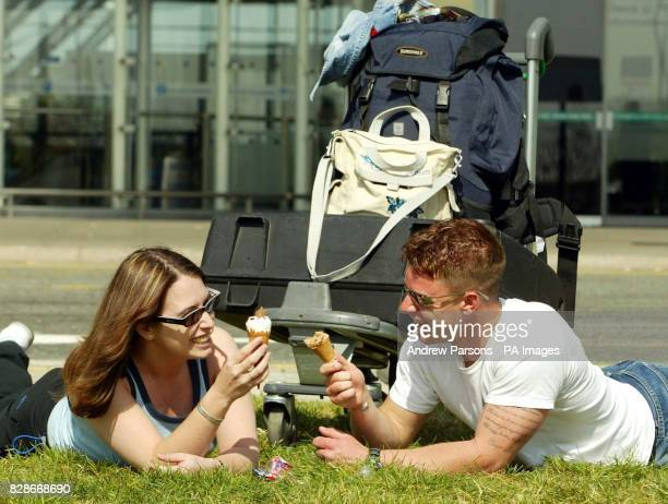 Vicki Leon eats an ice cream with her boyfriend Daniel Martin of Poole Dorset while sunbathing at Stansted Airport in Essex before catching a flight...