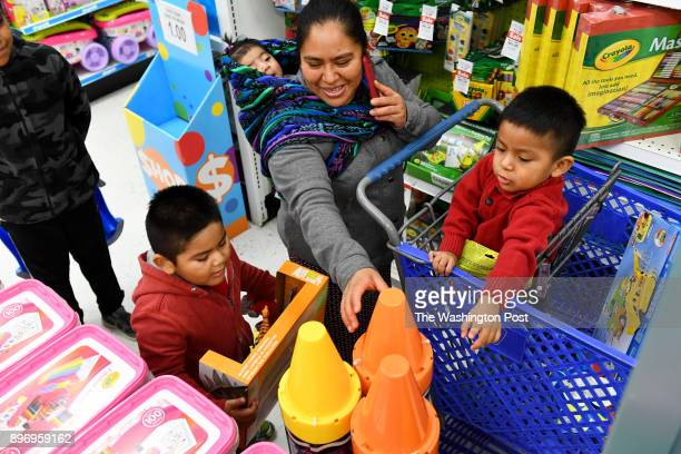 Vicki Lopez looks at giant crayon banks with some of her children including 6monthold Dayana on her back and Jerson left and Danny in the cart at...