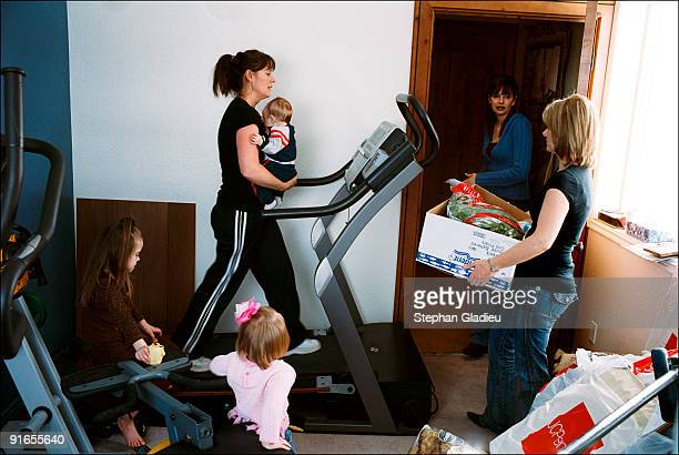 Vicki, one of three wives in a polygamist family consisting of one man, three women and 21 children, burns some calories on the home's treadmill with...