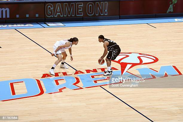 Vickie Johnson of the San Antonio Silver Stars brings the ball downcourt against Tamera Young of the Atlanta Dream during the WNBA game on June 18...