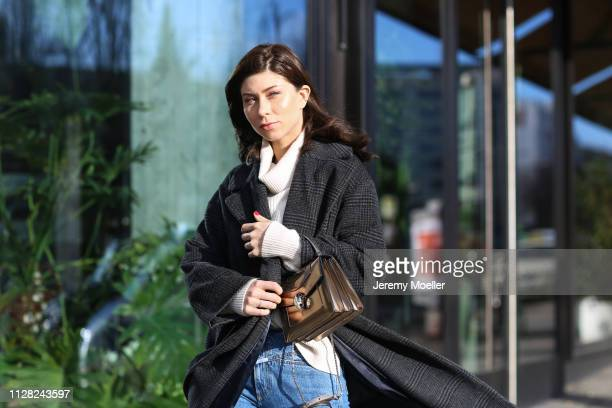 Vicky Heiler wearing Bulgari Bag, Louis Vuitton boots, Closed Jeans, Hallhuber sweater and Ganni coat on February 08, 2019 in Berlin, Germany.