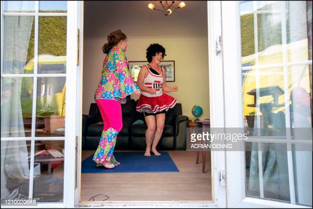 Vicky Sweeney and her daughter Alice exercise in their living room during a live online PE lesson on 'Fancy Dress Friday' at their home in Hartley...