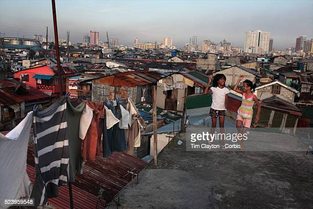 Vicky Valdez and Pinky Penaranda sing the latest pop hits as they dance on the roof tops in the Parola district of Tondo one of the worst slum areas...