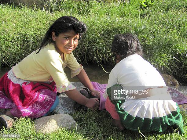 Vicos Peru Two Andean girls washing clothing in mountain stream
