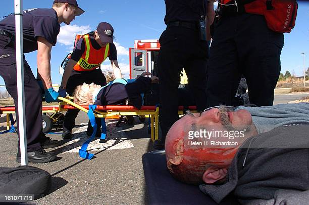 Victim Ernie Padilla <cq> lies in a stretcher while another victim is attended to by Aurora Firefighters in the triage area set up outside the Aurora...