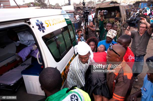 A victim is carried to an ambulance after two improvised explosive devices went off in Gikomba market on May 16 2014 in Nairobi Kenya Two improvised...