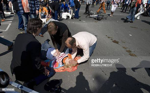 A victim is helped after a car crashed into the crowd waiting for the visit of the royal family in Apeldoorn on April 30 2009 Dutch Queen Beatrix and...