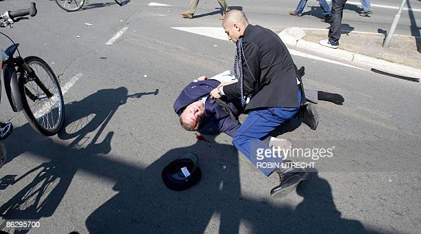 Victim is helped after a car crashed into the crowd waiting for the visit of the royal family in Apeldoorn on April 30, 2009. Dutch Queen Beatrix and...