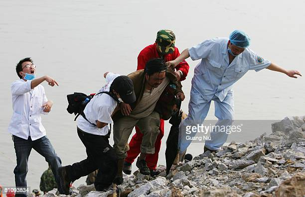 A victim is helped after being tansfered by by a military boat to Zipingba from Yingxiu county on May 15 2008 in Sichuan province Dujiangyan City...