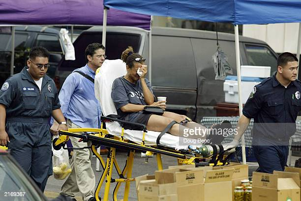 A victim is moved to triage after a car careened through a crowded farmers' market July 16 2003 in Santa Monica California At least eight people were...