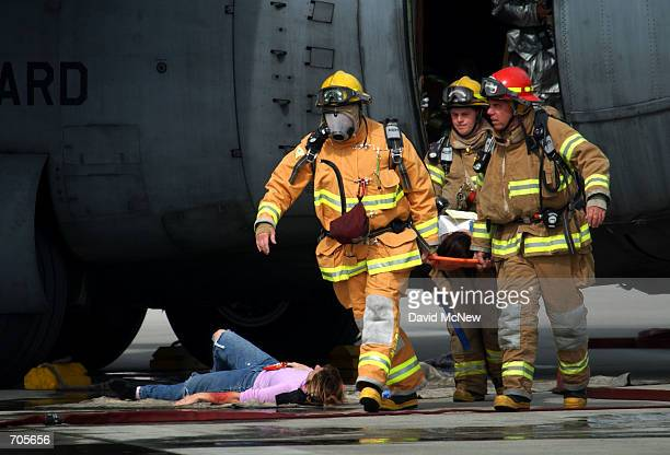 A victim lies on the tarmac as firefighters carry another from a Boeing 737300 aircraft during an FAArequired triennial emergency exercise at John...