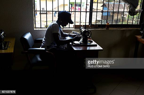 A victim of human trafficking in Libya sews clothes at Idia Renaissance nongovernmental organisation in Benin Edo State midwest Nigeria on October 21...