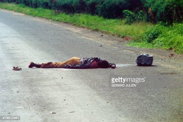 A victim of interethnic clashes between Hutus and Tutsis in Rwanda lies on a road near Kigali on May 12 1994 Rwanda's civil war continues after the...