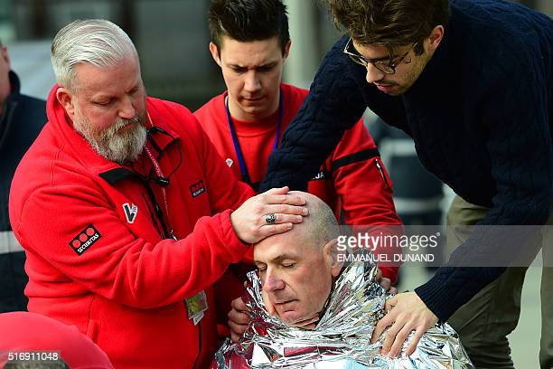 A victim receives first aid by rescuers on March 22 2016 near Maalbeek Maelbeek metro station in Brussels after a blast at this station near the EU...