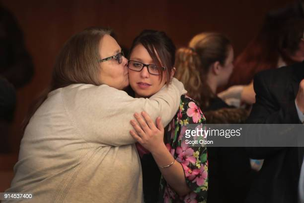 Victims and their family members embrace following the sentencing hearing for Larry Nassar in Eaton County Circuit Court on February 5 2018 in...