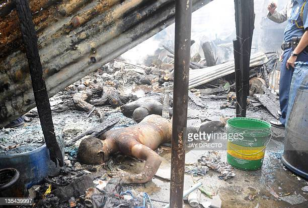 Victims bodies are seen at the site of a plane crash at a slum in Manila on December 10 2011 A fourseater cargo plane crashed onto a Philippine slum...