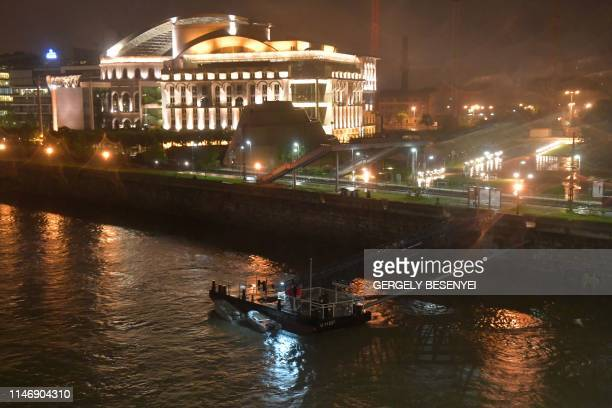 A victim's body is covered by a black plastic at Danube River close to the National Theatre of Budapest on May 29 2019 A river boat used for tourism...